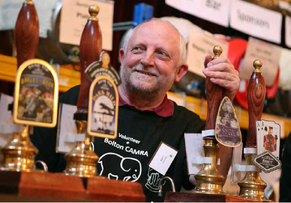 smiling bartender leaning over ale pumps with CAMRA t-shirt